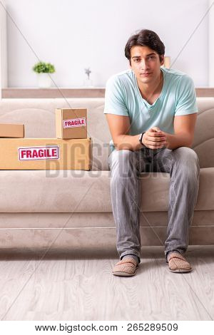 Man opening fragile parcel ordered from internet poster