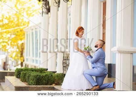 Just Married Loving Hipster Couple In Wedding Dress And Suit In The Park. Happy Bride And Groom Walk