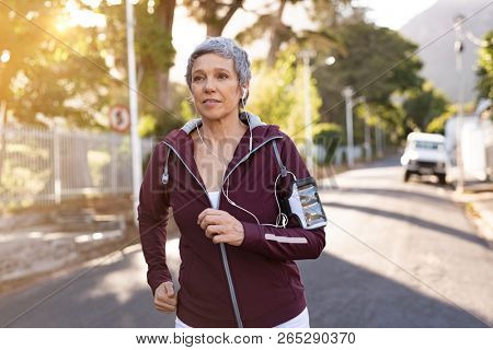 Senior woman jogging on street during late afternoon. Healthy mature woman running while listening to music with earphones. Active mature lady jogging in the city street at sunset.