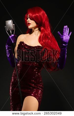 Young Romantic Redhead Woman With Very Long Hair In Red Dress With Microphone On The Stand Sings On