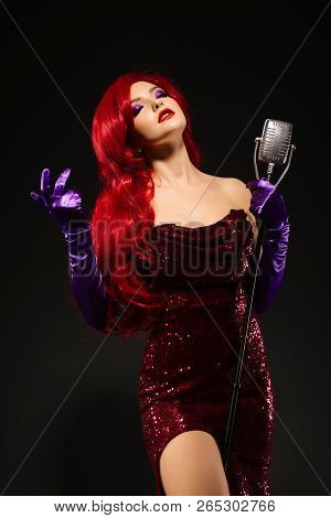 Young Romantic Redhead Woman With Very Long Hair In Red Dress With Microphone On The Stand Sings Wit