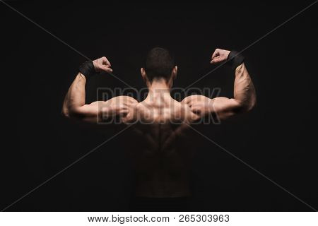 Unrecognizable Man Bodybuilder Shows Strong Hands And Back Muscles, Athletic Trapezius. Low Key, Stu