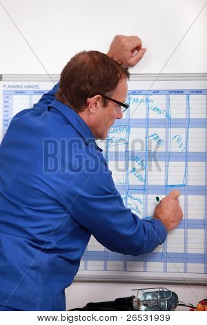 Manual worker writing on a wall planner