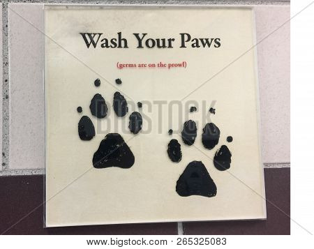 A Amusing Sign Outside A Public Convenience Telling People To Wash Their Paws