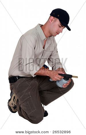 A manual worker examining a welding torch.