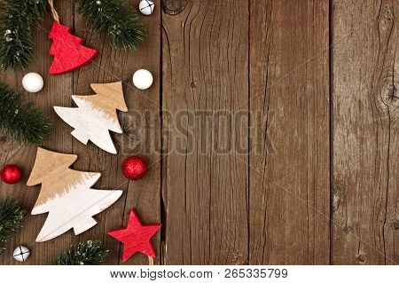 Christmas Side Border Of Traditional Wooden Decorations And Tree Branches On A Rustic Wood Backgroun