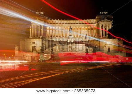 The monument of Vittorio Emanuele II in central Rome illuminated at night with light trails from the passing traffic