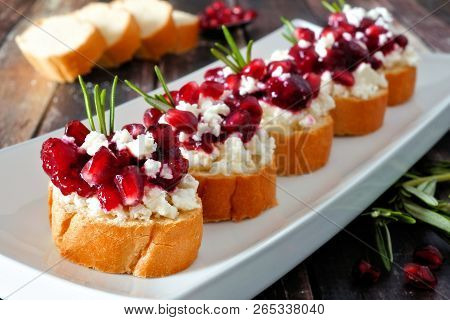Holiday Crostini Appetizers With Cranberries, Pomegranates And Feta Cheese. Close Up On A Serving Pl
