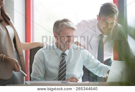 Senior business man laughing and smiling whilst he shows his two colleagues what is on his computer. This is a positive image from the small real life business series