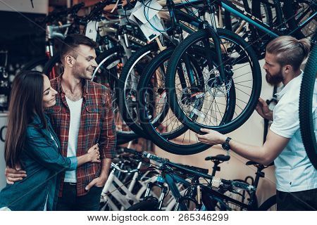 Consultant Helps Young Couple In Bike Choosing. Bearded Shop Assistant Shows Wheel To Beautiful Girl
