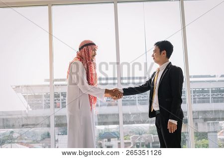 Arab And Asian Business Partners Stand Together After Successful Business Talks.two Businessmen Shak