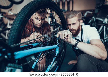 Guy And Bike Mechanic Repairs Bicycle In Workshop. Closeup Portrait Of Young Caucasian Man Wearing A