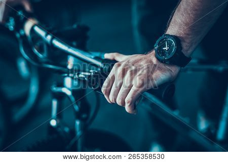 Closeup Of Male Hand Holds Cycle Handlebar. Mans Muscular Hand Wearing Modern Black Stylish Hand Wat