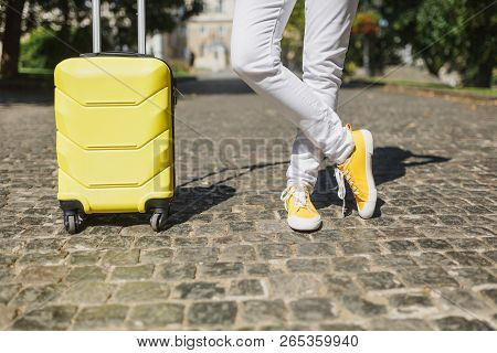 Cropped Image Traveler Tourist Woman Crossed Legs In Yellow Summer Casual Clothes With Suitcase On R