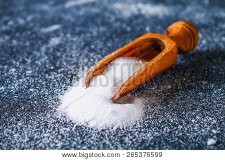 Crystals Of Shallow Salt In A Scoop, Spoon On A Dark Gray Table.
