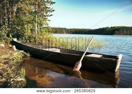 Primitive Wooden Boat Of Northern Peoples (veps Region) With One Oar For Alternate Rowing From Right