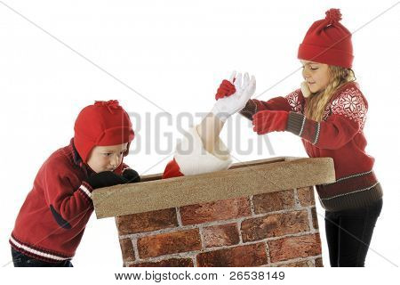 Two young children trying to help Santa back up the chimney.  On a white background.