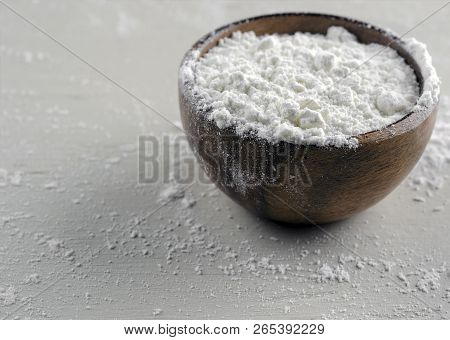 Close Up Photograph Of A Small Wooden Bowl Of Whole Wheat Unbleached Flour On A Messy Painted Surfac