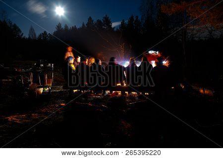 People Sit At Night Round Bright Bonfire