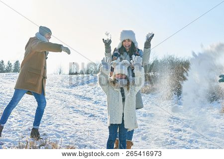 Family in snowball fight having fun with joy in winter