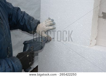 Wall Insulation. Builder Drilling Wall For Installing Anchors To Hold Rigid Insulation Foam Board. A