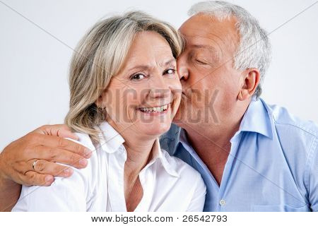 Close-up portrait of woman being affectionately kissed by her husband