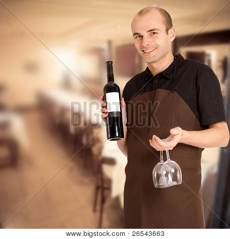 Smiling sommelier presenting a wine bottle with a blank label and a pair of glasses in a restaurant