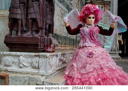 Colorful Carnival Rosa-pink Mask And Costume At The Traditional Festival In Venice, Italy