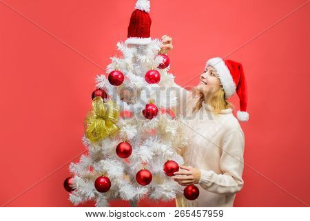 Decorate Christmas Tree. Preparing For Winter Holidays. Happy Girl In Santa Hat Decorating Christmas