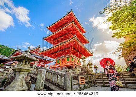Kyoto, Japan - April 24, 2017: Woman Wear Kimono And Parasol Standing In Red Pagoda Of Kiyomizu Temp