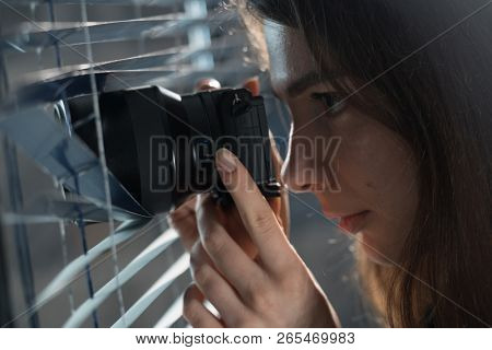 Young woman Paparazzi take a photo suspiciously from around a blinds  while using a camera. GDPR Concept poster