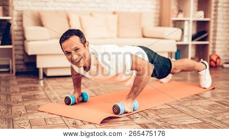 Push Ups On Floor With Dumbbells. Father Spotting. Sport At Home. Warm Up In Quarter. Lying On Gym M