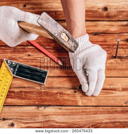 Hammering A Nail Into Wooden Board. Hammering A Nail Into The Wall. Concept Of Renovation, Housework
