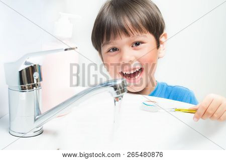 Little Boy Brushing His Teeth With A Toothbrush