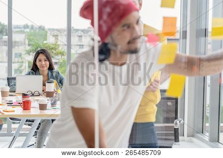 Closeup Asian Woman Working Which Have Photo Blurred Of Creative Writing And Pointing The Postit On