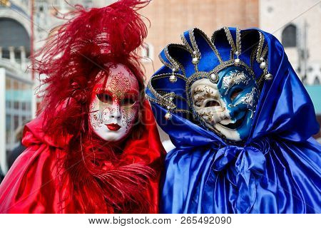 Colorful Carnival Pair Red-blue Mask And Costume At The Traditional Festival In Venice, Italy