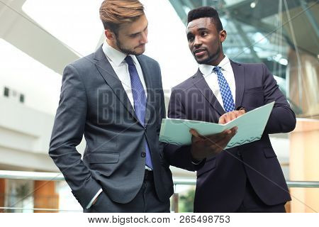 Two Multinational Young Businessmen Discussing Business At Meeting In Office.