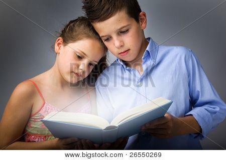 Image of smart children reading interesting book