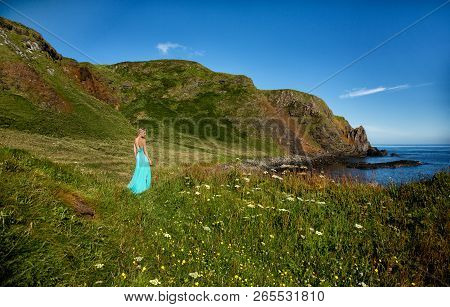 Beautiful Blonde Woman In Turquoise Green Long Dress, At Sea Shore Next To A Medieval Ruin In Irelan