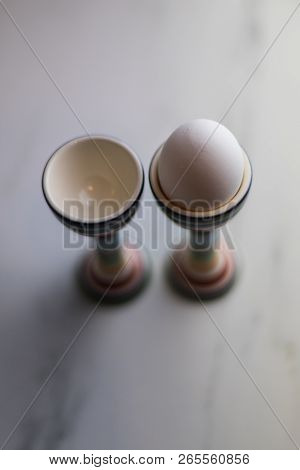Two Eggcups On A Marble Table With Colorful Stripes And Only One Egg