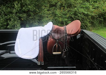 English Type Saddle And Soft Saddle Shaped Blanket Sitting On The Back Of A Pickup Truck Bed.