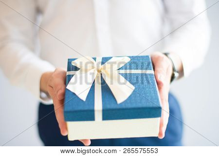 Closeup Of Man Giving Big Gift Box With Bow. Person Greeting Someone. Gift Concept. Isolated Cropped
