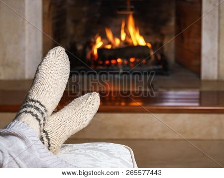 Feet In Woollen Socks And Knitted Plaid In Front Of The Fireplace. Close Up On Feet. Cozy Relaxed Ma