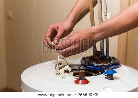 Master Hands Hold Wires Of Water Heater