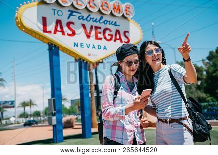 Beautiful Sisters Standing In Front Of The Las Vegas Sign And Going To Visit The City. Welcome To Fa