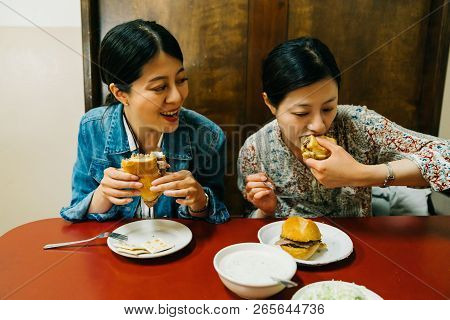 Hungry Ladies Sitting In The Red Table And Joyfully Eating Hamburgers. Asian Sisters Having Lunch At