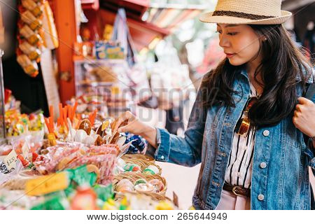 Elegant Lady Choosing Sweets At The Candy Vendor In The Traditional Market. Traveler Looking At The