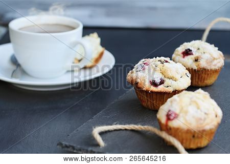 Cranberry Muffins On A Slate Serving Tray With Open Muffin With Butter And A Steaming Hot Cup Of Cof
