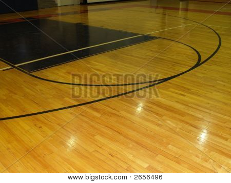 A wood floor on an indoor basketball court. poster
