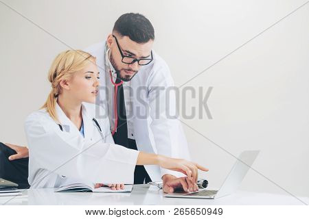 Doctor At Hospital Works On Computer With Partner.